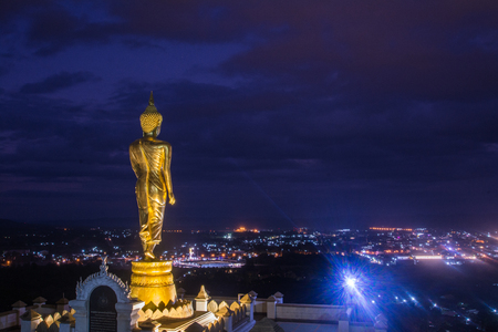 Golden Buddha standing on a mountain at sunset twilight  in Nan Province, Thailand.
