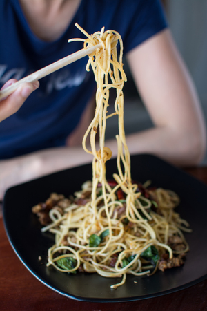 woman eating stir-fried spaghetti with Sai Aua (Notrhern Thai Spicy Sausage)