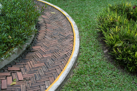 red brick walkway in the garden with green grass Archivio Fotografico - 101031283