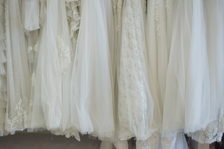 white wedding dresses hanging on racks Archivio Fotografico - 101703823