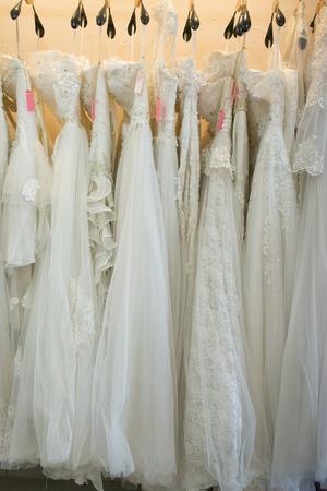 white wedding dresses hanging on racks Archivio Fotografico - 101631404
