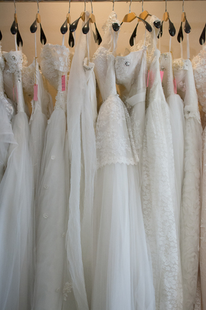 white wedding dresses hanging on racks Archivio Fotografico - 101678340