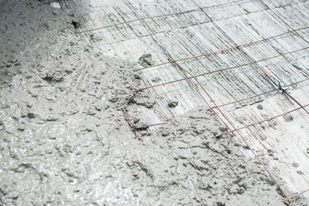 The wet concrete is poured on wire mesh steel reinforcement Archivio Fotografico