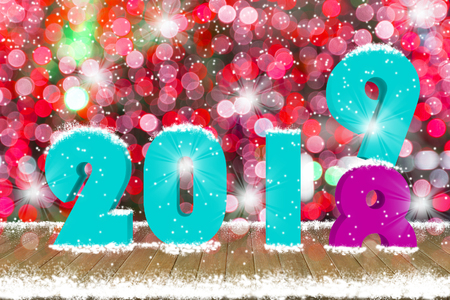 2019 Text on wood table top with snow and decorative light bokeh background