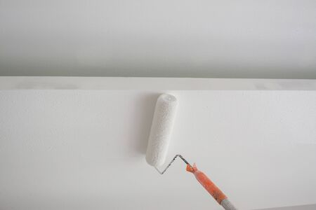 painting a white gypsum plaster ceiling with paint roller Reklamní fotografie