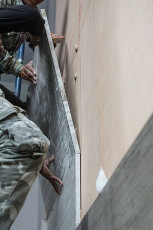 laying marble on wall, installing marble  in construction site.