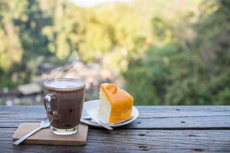 Coffee cup and orange cake on the wooden table with nature landscape background.