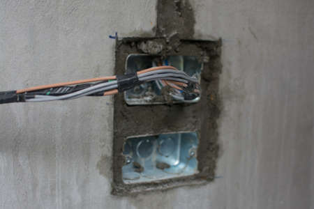 electric system on wall in construction site ,outlet with iron pipes