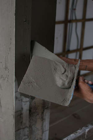 Plasterer Cconcrete worker at wall of house construction