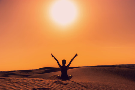Silhouette of a girl sitting on sand raising her arms up during the sunset, feeling happy and free Stok Fotoğraf