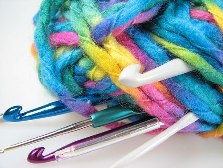YARN WITH DIFFERENT SIZE OF CHROCHET HOOKS OVER WHITE photo