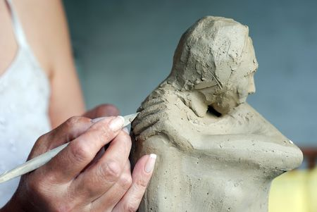 sculptor: Close up to woman artist hands while she is creating a sculpture