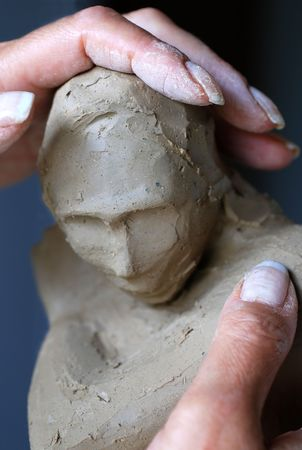 Close up to woman artist hands while she is creating a sculpture
