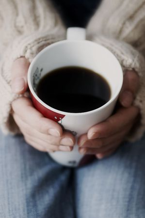 Hands holding cup of dark coffee photo