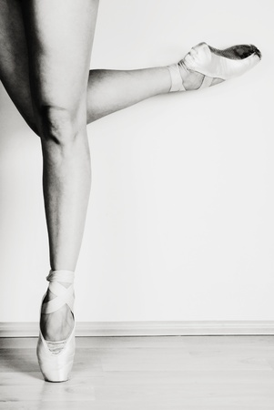 Ballerina dancing on pointe in studio, black and white studio shot photo