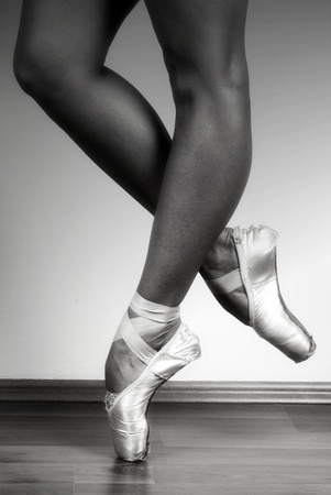 ballerina shoes: Ballerina dancing on point in studio, black and white ND filtered Stock Photo