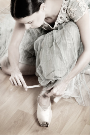desaturated colors: Ballerina tying her old worned pointe shoes before her rehearsal, glimmer and soft focus , desaturated colors with low contrast in studio