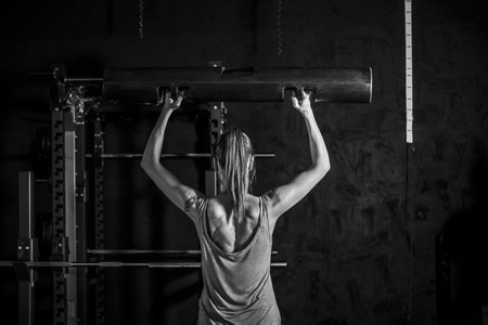 showing muscles: Fitness  Strong woman showing muscles of her back and hands while training weightlifting on black background