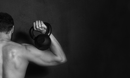 arm muscles: Bodybuilding Strong Man showing muscles of his back and arm while training with dumbbell on black background
