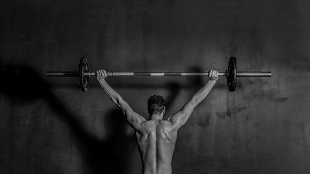 fitness hombres: Bodybuilding Hombre fuerte que muestra los músculos de la espalda y los brazos mientras que el entrenamiento con barra sobre fondo negro BW foto