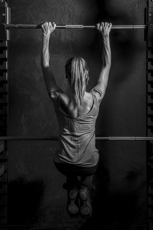 woman muscle: Fitness Strong Woman showing muscles of her back and hands while training weightlifting on black background Stock Photo