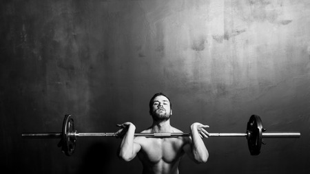 Bodybuilding Young Athletic Strong Man Weightlifting  Black and White in studio