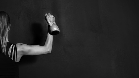 Fitness Athletic Strong Woman Workout with Dumbbell showing biceps on black background Foto de archivo