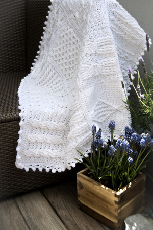 cable knit: Crochet, Cable Knit Afghan Baby Blanket in White on Sofa with Lavender Stock Photo