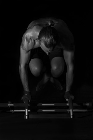 strong arm: Body Workout Strong Man Arm Balance on Black Background,  high contrast low exposure with vignette  black and white photo  in studio