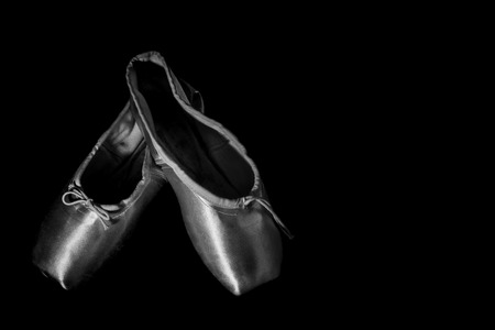 ballet slipper: Ballet Shoes isolated on Black Background, high contrast with vignette black and white in studio Stock Photo