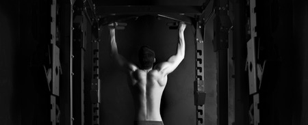 pull up: Muscle athlete man in gym making elevations. Bodybuilder training in gym . Black and white High Contrast in studio Stock Photo