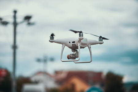 Runnnig white drone in the city in a cloudy day Stock Photo
