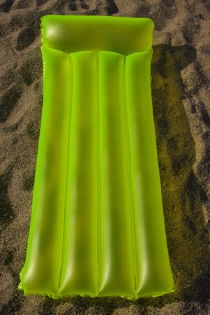 blow up: green airbed lying on a sand on a beach in Costa Brava - Spain Stock Photo