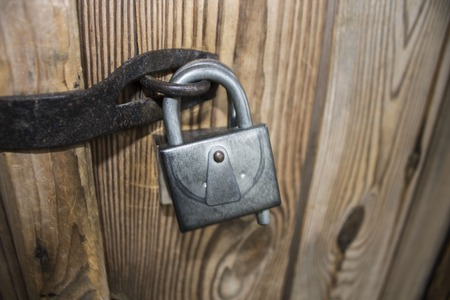 ensuring: Old lock on a wooden door of the gate, Ukraine, Lviv