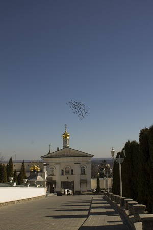 red cross red bird: Birds fly over the Orthodox tserkovyuv Pochayevskaya Lavra, Ukraine Stock Photo