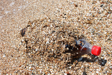 corked: Plastic bottle washed up on a sandy beach