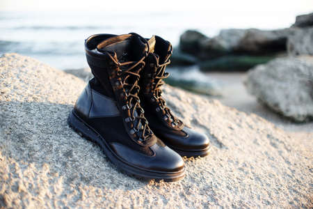 Men's green and beige boots in military style with laces for active walks in the mountains and fishing on a background of sand and grass. Caucasus, Russia