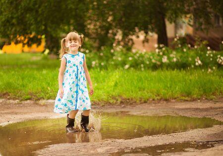 Little kid girl runs through a puddle. summer outdoor