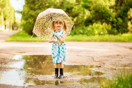 happy child girl with an umbrella and rubber boots in puddle on summer walk Archivio Fotografico