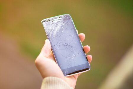 young man hold broken smartphone screen. Broken phone screen in hand