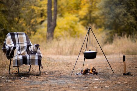 Relaxing and preparing food on campfire in camping, autumn rest outdoors in forest