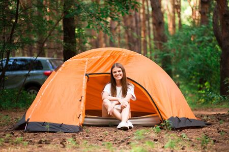 beautiful woman sitting outside the tent in free alternative vacation camping in the forest. different lifestyle concept