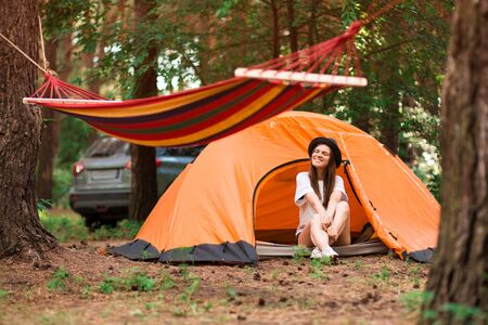beautiful woman sitting outside tent enjoying holiday away from bustle of city in forest. Lifestyle concept