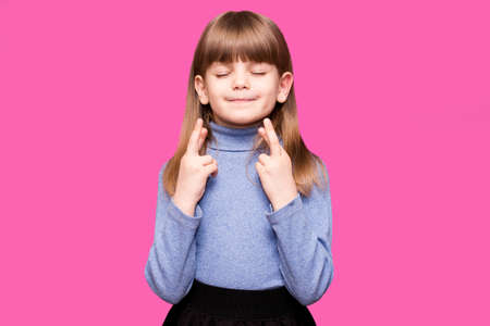 Funny little girl crossing fingers, hoping her wish come true, isolated on pink background. Portrait of small girl praying, wishing good luck or miracle. 写真素材