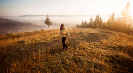 Carefree happy woman in yellow shirt and straw hat enjoying nature on grass meadow on top of mountain with sunrise. Beauty girl outdoor with sunbeams. Freedom concept