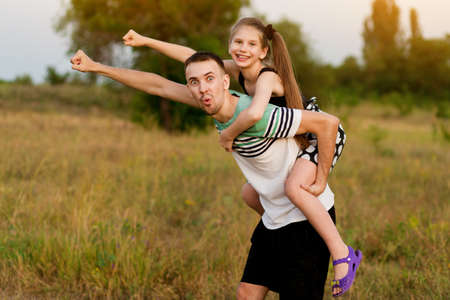 Superhero father shows his daughter superhero outdoors. Concept photo of  childhood, fatherhood and parenthood. Stock fotó