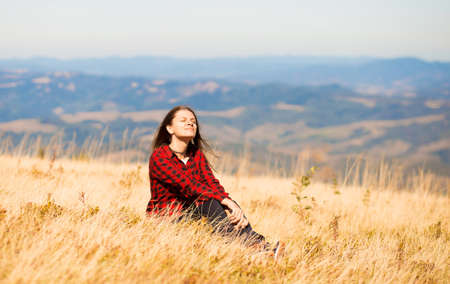 Carefree happy woman sitting on meadow on top of mountain enjoying sun on her face. Freedom. Enjoyment. Daydreaming