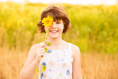 Joyful girl smiling and covering face with sunflower in summer field Archivio Fotografico