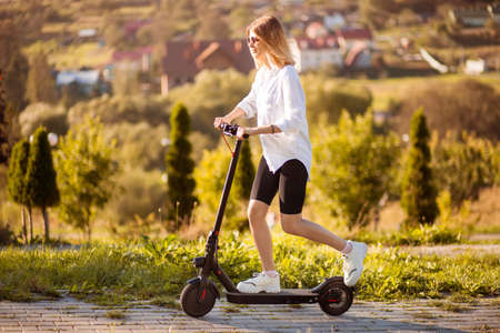 Young beautiful stylish woman riding electric scooter to work, modern girl, new generation, electric transport, ecological transport 免版税图像