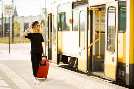 Stylish woman wear total black with red travel suitcase stands at city stop awaiting tram